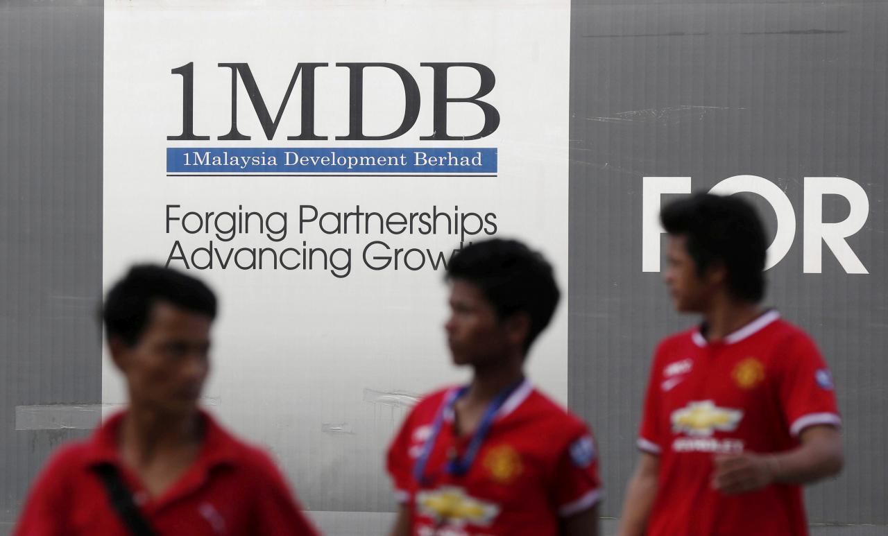 Men walk past a 1Malaysia Development Berhad (1MDB) billboard at the fund's flagship Tun Razak Exchange development in Kuala Lumpur March 1, 2015. — Reuters pic
