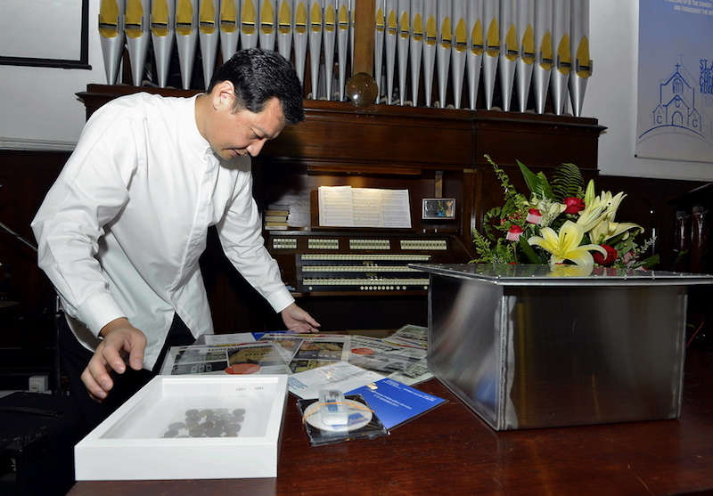 St Andrew's Secretary Centenary Steering Committee member Kenneth Tan arranges all the items that will be placed in the second time capsule. — Picture by Ham Abu Bakar