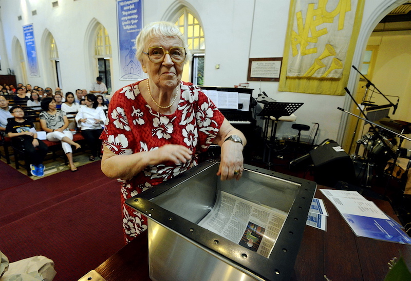 Parishioner of St Andrew's Church, Joyce Keep, places Malay Mail articles in the second time capsule. — Picture by Ham Abu Bakar