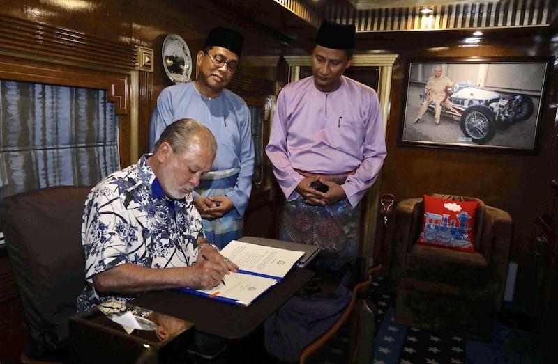 Sultan Ibrahim signs the instrument of dissolution, as Johor Mentri Besar Datuk Seri Mohamed Khaled Nordin and state secretary Datuk Azmi Rohani look on, at Istana Pasir Pelangi in Johor Baru April 6, 2018. — Bernama pic