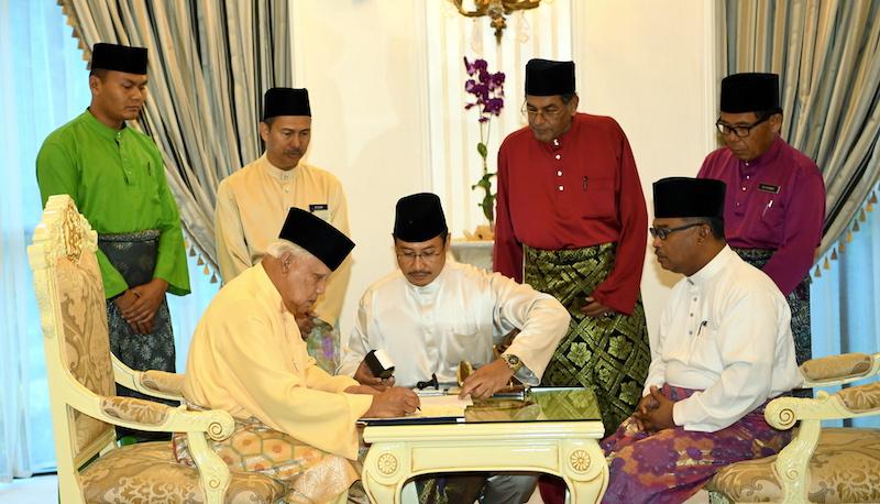 Yang Dipertua Negeri of Melaka Tun Mohd Khalil Yaakob signs the instrument of dissolution, as Melaka Chief Minister Datuk Seri Idris Haron looks on, in Melaka April 6, 2018. — Bernama pic