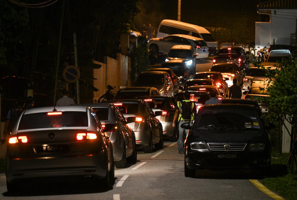 Police cars enter the road leading to former prime minister Datuk Seri Najib Razak's residence in Kuala Lumpur May 16, 2018. — AFP pic