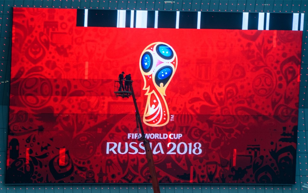 Workers fix a giant screen featuring the Russian Fifa World Cup logo, mounted outside Rostov Arena in the southern Russian city of Rostov-on-Don May 12, 2018. — AFP pic