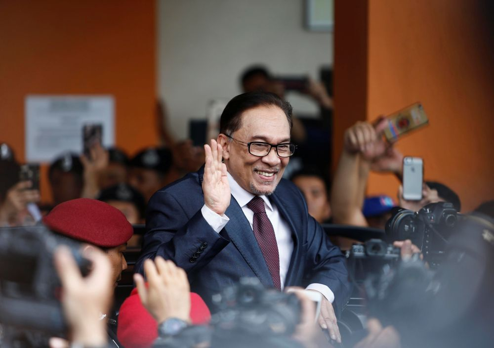 Datuk Seri Anwar Ibrahim waves to the crowd as he leaves the Cheras Rehabilitation Centre in Kuala Lumpur on May 16, 2018. — Reuters pic