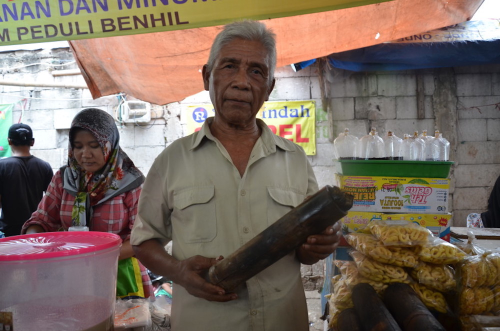 Mawi stands proudly with his homemade lemang at Benhil Market. — Jakarta Globe pic
