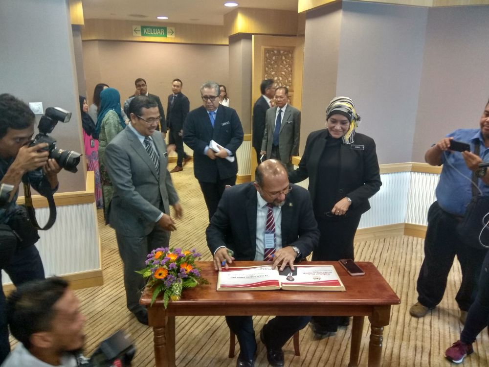 Gobind signs his attendance before a briefing session with department heads while chief secretary Tan Sri Sharifah Zarah Syed Ahmad (right) looks on, May 22, 2018. ― Picture by Kenneth Tee