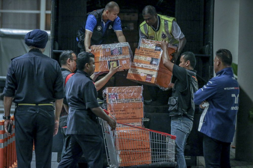 File photo showing investigators lifting sealed boxes believed to contain luxury designer bags onto a Black Maria outside Pavilion Residences in Kuala Lumpur May 18, 2018. — Picture by Hari Anggara