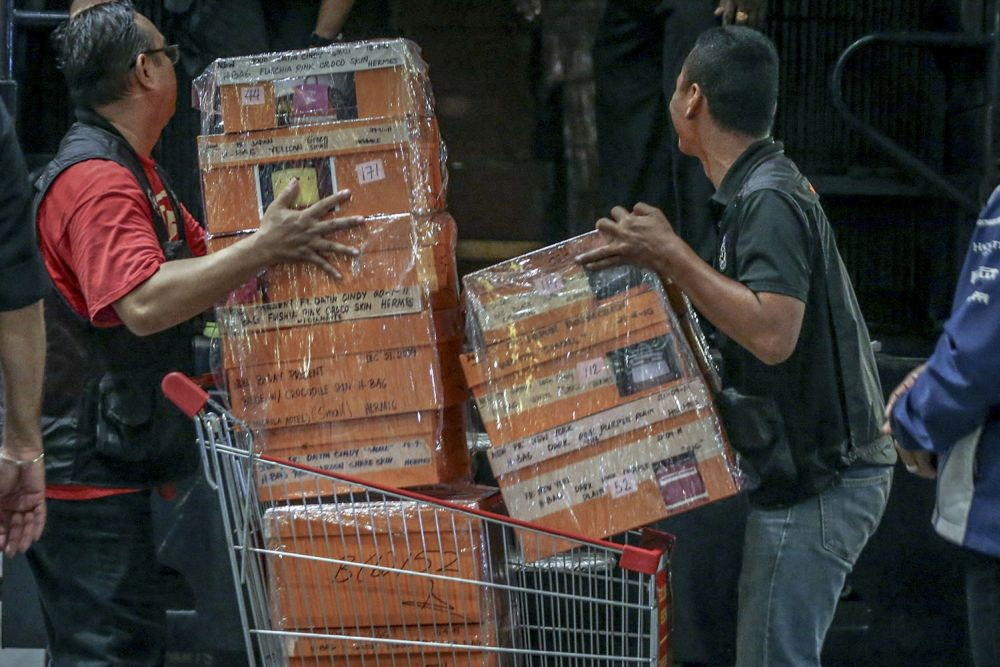 Investigators lift sealed boxes believed to contain luxury designer bags onto a Black Maria outside Pavilion Residences in Kuala Lumpur May 18, 2018. — Picture by Hari Anggara