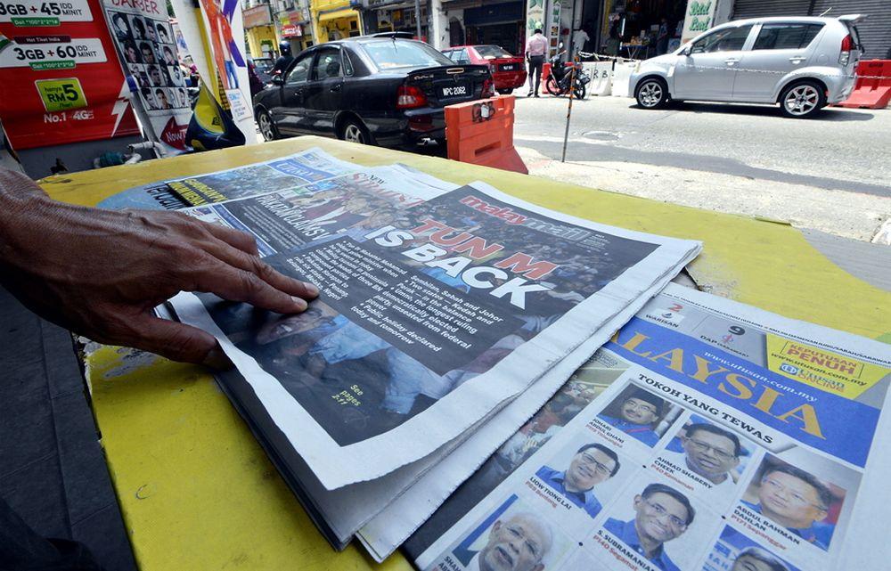 A man reads the newspaper at a shop in Lebuh Ampang, Kuala Lumpur May 10, 2018. ― Picture by Ham Abu Bakar