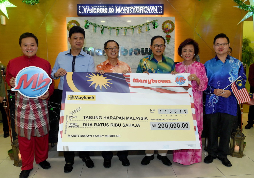 Marrybrown chairman Datuk Lawrence Liew (3rd right), Marrybrown managing director Datuk Nancy Liew (2nd right) and Tebrau MP Steven Choong Shiau Yoon (3rd left) pose with a mock cheque for Tabung Harapan Malaysia in Johor Baru June 11, 2018 — Bernama pic