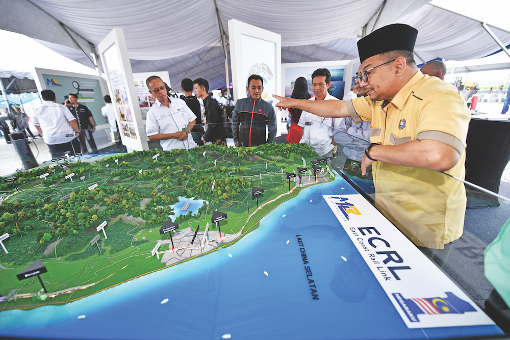 A man looks at a map of the East Coast Rail Link (ECRL) during a ground-breaking ceremony in Tunjong, Kota Baru, April 11, 2018. — Bernama pic