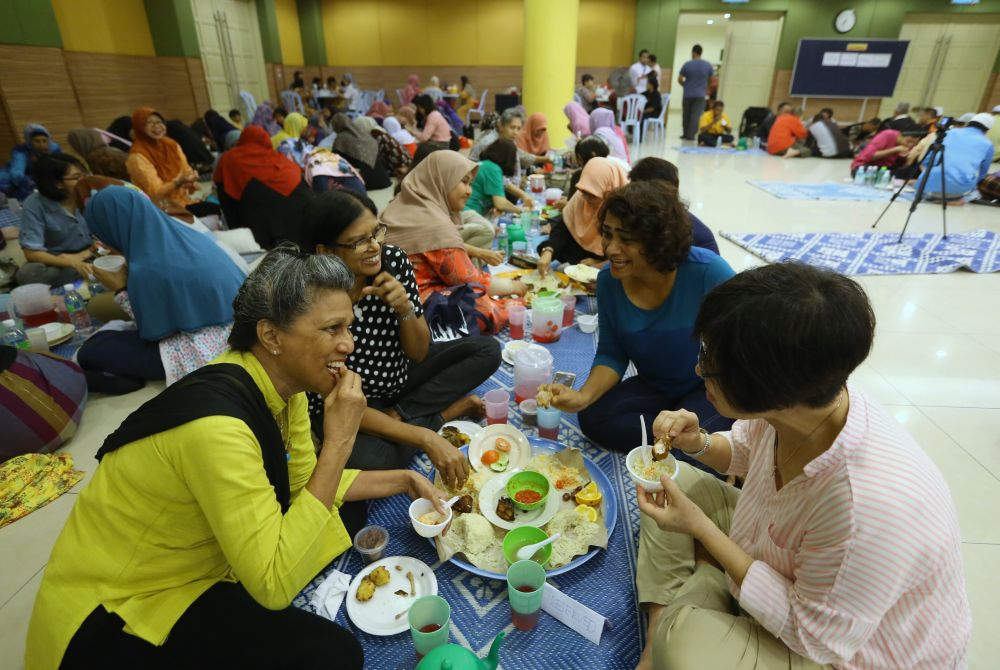 Participants share their meals in a huge tray and eat together right after the Maghrib azan. — Picture by Zuraneeza Zulkifli
