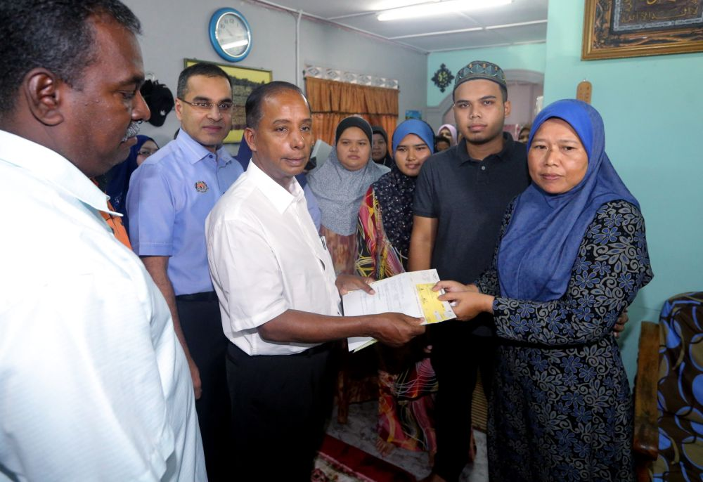 Kulasegaran hands over Socso contribution to Rozaini Ibrahim, widow of late bus driver Shuaib KK Mohamed Unny, at the family's home in Kamunting June 8, 2018. — Picture by Farhan Najib