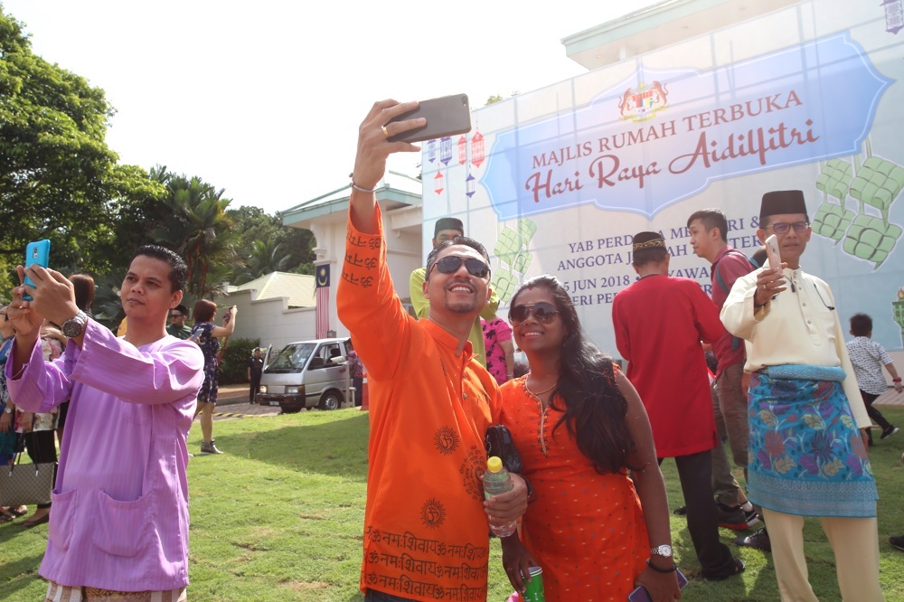 People take selfies during the prime minister's Aidilfitri open house in Putrajaya June 15, 2018. — Picture by Choo Choy May