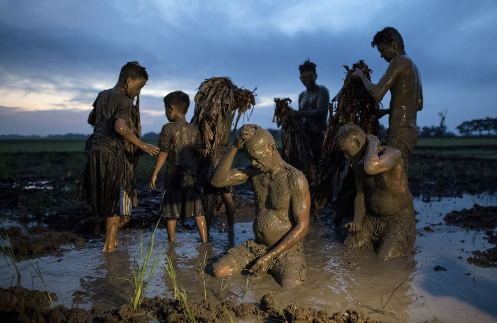 Devotees cover themselves with mud as they prepare to head to church to attend a mass as part of a religious festival in honour of St John the Baptist, in Aliaga town, north of Manila, on June 24, 2018. — AFP pic