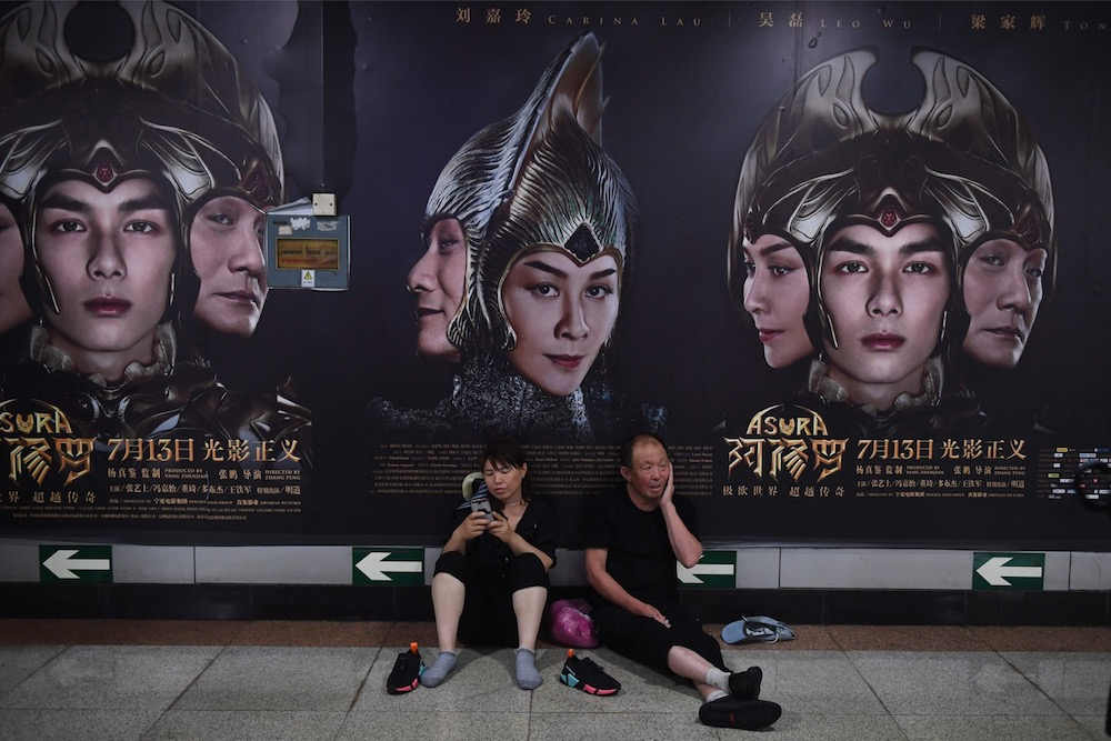 A man and woman rest in front of posters for the movie Asura at a subway station in Beijing July 17, 2018. — AFP pic