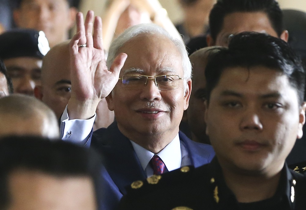 Former prime minister Datuk Seri Najib Razak wave at the media as he enters Criminal High Court 3 at the Kuala Lumpur Courts Complex July 4, 2018. — Picture by Azneal Ishak
