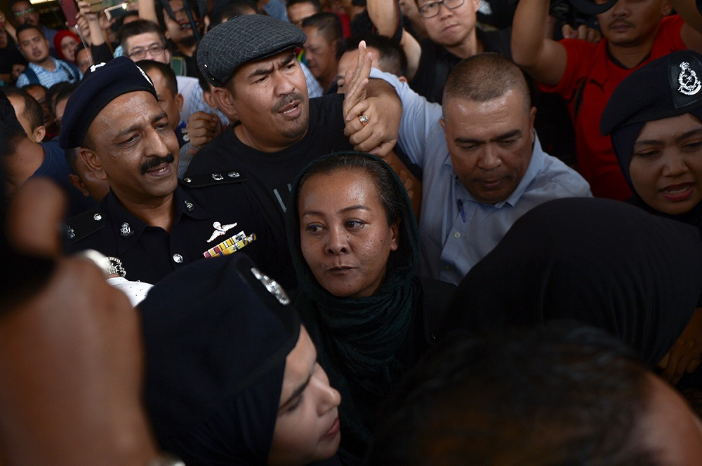 Actress Ellie Suriaty Omar (centre) is escorted by the police after causing a ruckus during Attorney General Tommy Thomas' press conference at the Kuala Lumpur Courts Complex July 4, 2018. — Picture by Mukhriz Hazim