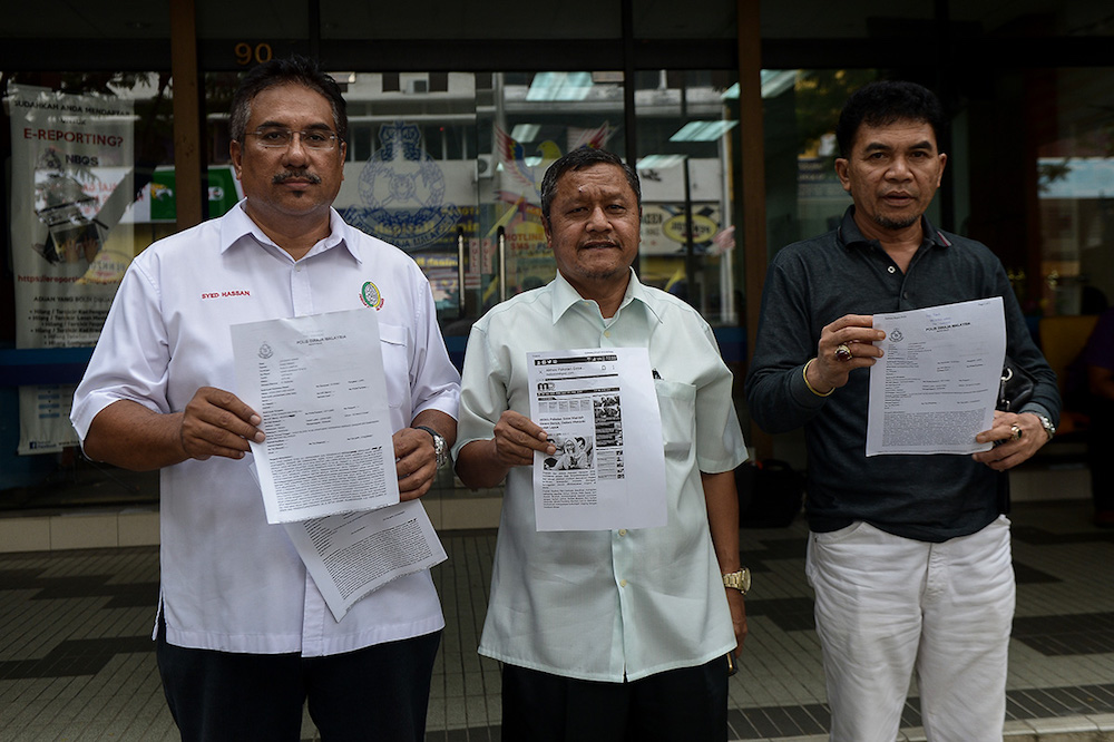 (From left) Perkasa secretary-general Syed Hassan Syed Ali, information chief Datuk Roslan Kasim and Perkasa Kelantan vice-president Datuk Che Abdullah Che Ismail pose for pictures after lodging a police report at Putra police station in Kuala Lumpur July 10, 2018. — Picture by Mukhriz Hazim