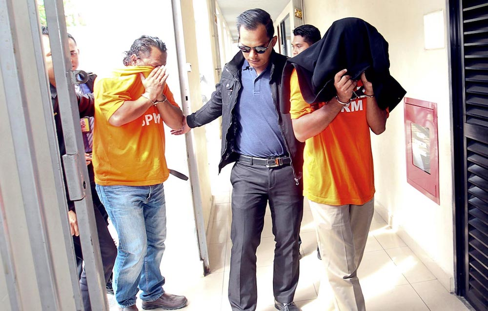 A former Penang Forestry Department assistant engineer and a company owner are brought to their remand hearing by MACC personnel in George Town July 18, 2018.