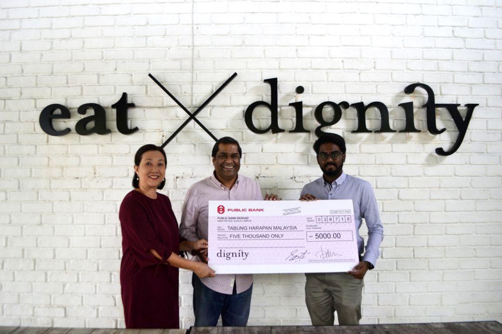 Dignity for Children Foundation's founders Petrina Satvinder and Rev. Elisha Satvinder handing over the mock cheque to Prabakaran. ― Picture courtesy of Dignity for Children Foundation