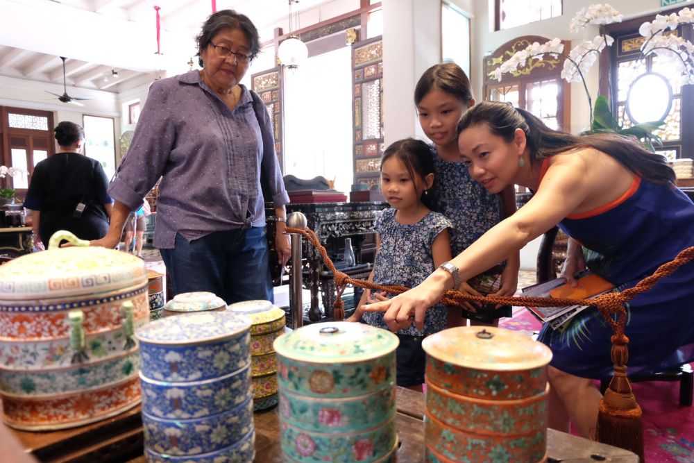 Visitors looking at the colourful porcelain tingkat on display at Seven Terraces.