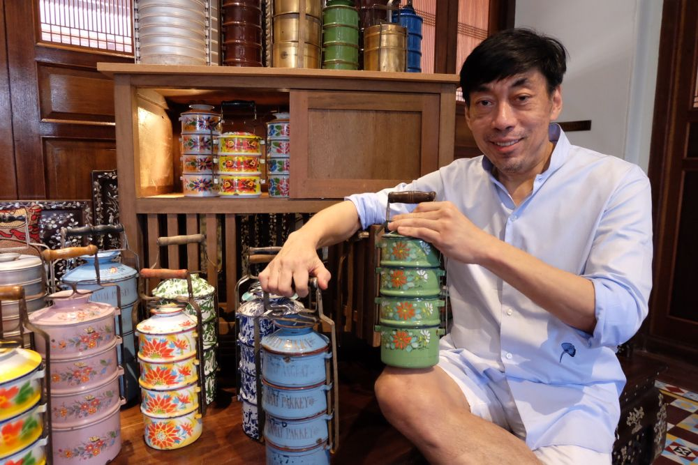 GTHH founder Chris Ong holding the two tiffin carriers that held bittersweet memories for him as those belonged to his parents. ― Pix by KE Ooi
