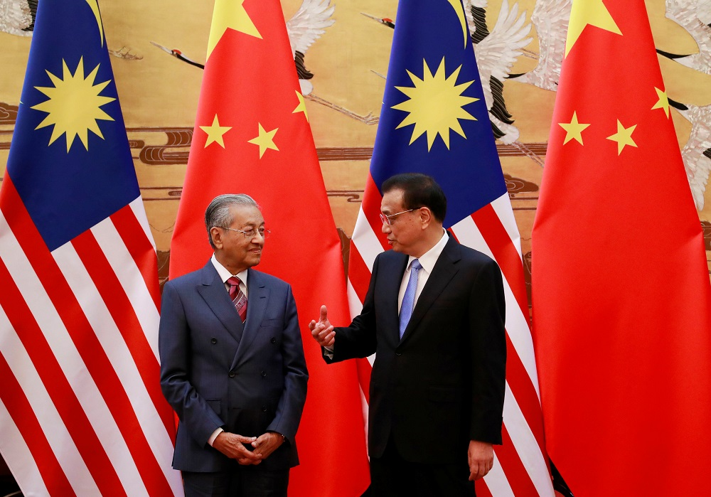 Prime Minister Tun Dr Mahathir Mohamad and China's Premier Li Keqiang chat during a signing ceremony at the Great Hall of the People in Beijing August 20, 2018. — Reuters pic