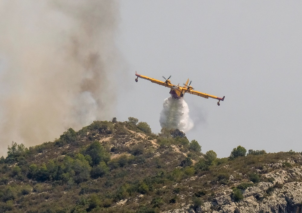 A firefighter plane drops water on a wildfire in Llutxent, near Valencia, Spain, August 7, 2018. — Reuters pic