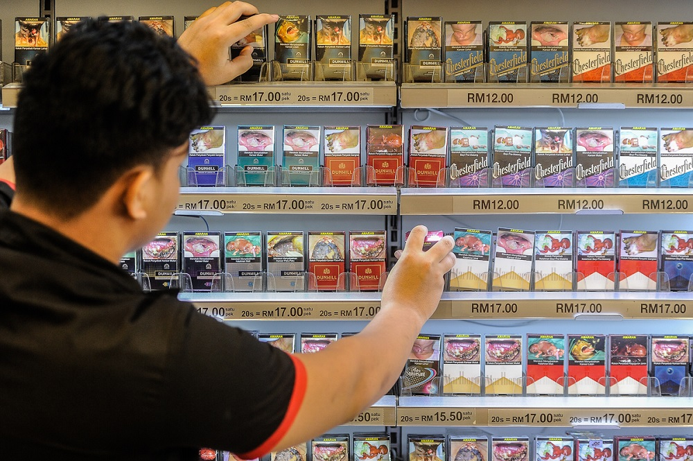 A worker arranges cigarette packets at a shop in Putrajaya September 5, 2018. — Picture by Shafwan Zaidon