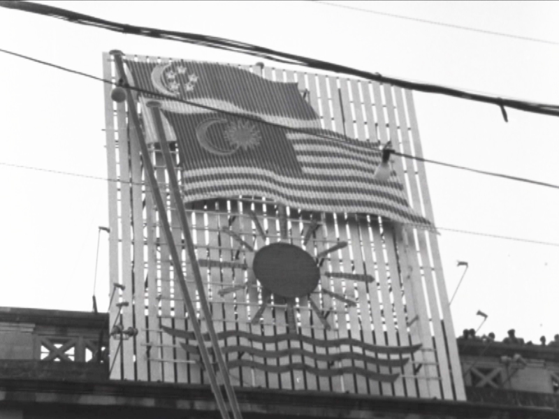 Singapore's flag is shown here with Malaysia's flag. Singapore was part of Malaysia from September 16, 1963 until August 9, 1965. — Screen capture via Reuters archive footage