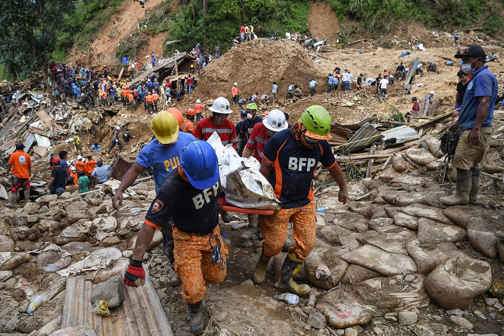 Rescuers carry a body bag containing a landslide victim, triggered by heavy rains during Typhoon Mangkhut, in Itogon, Benguet province on September 18, 2018. — AFP pic