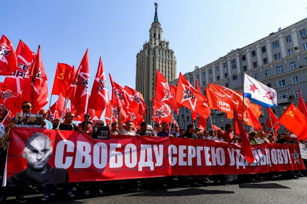 File picture shows Russian left-wing movement activist carrying red flags and the banner read as 'Freedom for Sergei Udaltsov' as they take part in a rally against the government's proposed reform hiking the pension age in Moscow on September 2, 2018. — AFP pic