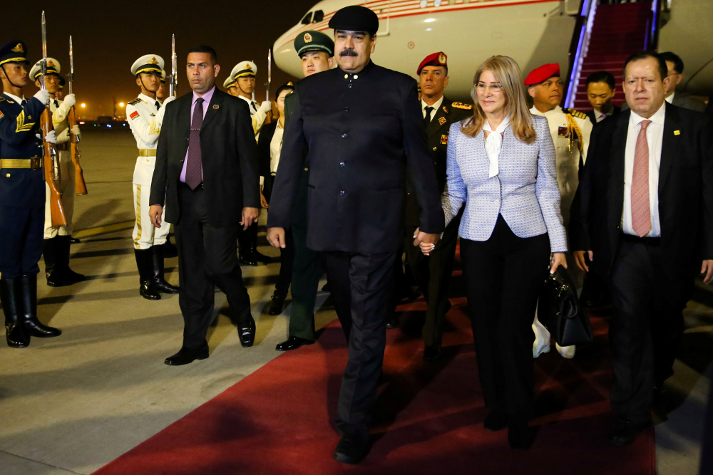 Venezuela's President Nicolas Maduro walks with his wife Cilia Flores upon their arrival at the airport in Beijing September 13, 2018. — Handout by Miraflores Palace via Reuters