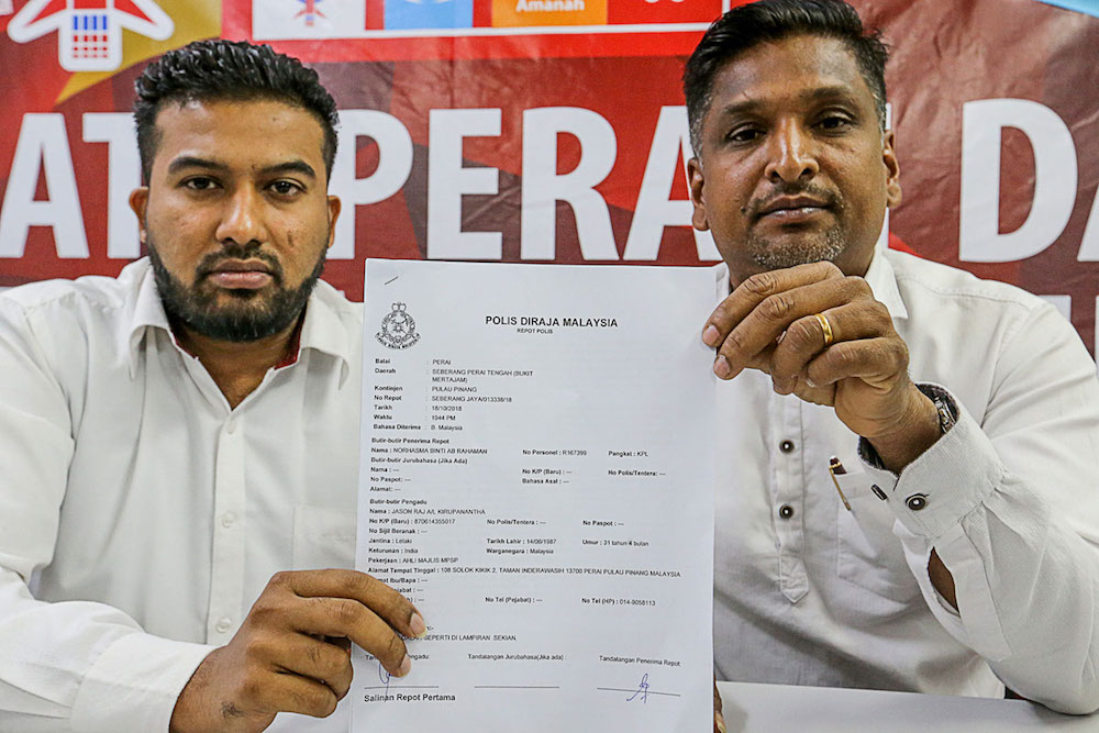 K Jason Raj (left) and P.David Marshel show the police report made against the immigration officer during a press conference at the Perai Service Centre. — Picture by Sayuti Zainudin