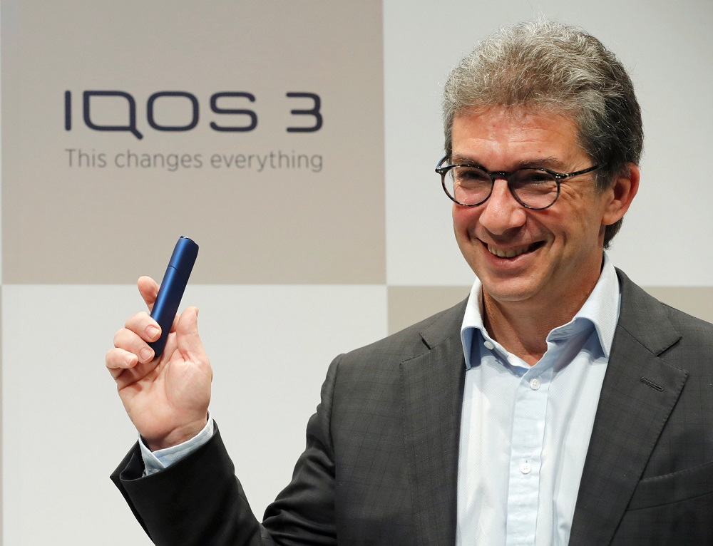 Philip Morris International's CEO Andre Calantzopoulos poses with the new IQOS 3 devices at a news conference in Tokyo October 23, 2018. — Reuters pic