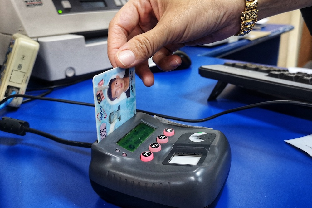 A MyKad identification card reader in use at a POS Malaysia outlet in Bangi October 15, 2018. Justice for Sisters has recommended that trans and gender diverse people be allowed to change their gender on their legal documents based on their gender identity. — Picture by Shafwan Zaidon