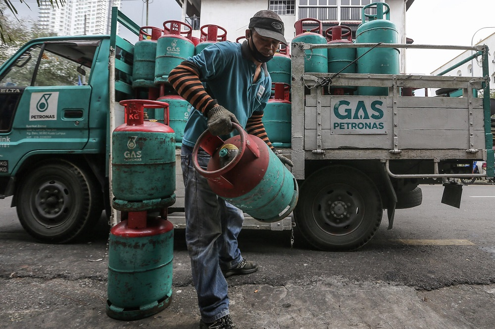 A worker unloads gas cylinders from a truck at Kampung Baru in Kuala Lumpur October 31, 2018. — Picture by Hari Anggara