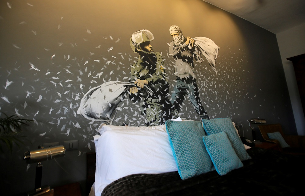 A graffiti work painted by street artist Banksy showing an Israeli soldier and masked Palestinian youth having a pillow fight, is seen in the Walled Off hotel in Bethlehem, in the occupied West Bank, October 23, 2018. — Reuters pic