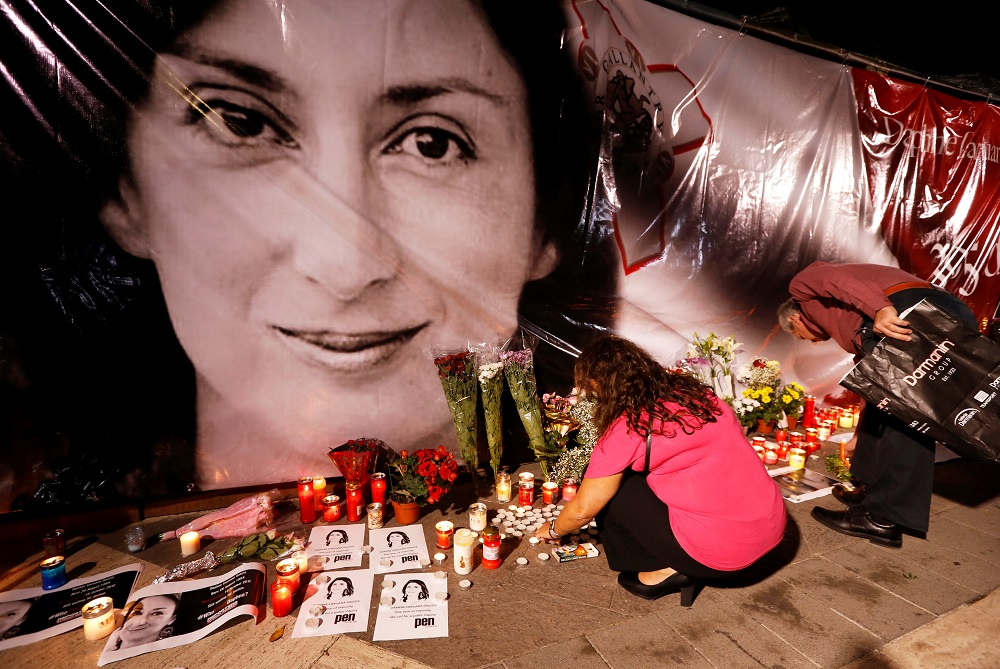 People lay flowers and candles at a makeshift memorial during a vigil and protest on the first anniversary of the assassination of Daphne Caruana Galizia in a car bomb, outside the Courts of Justice in Valletta, Malta October 16, 2018. — Reuters pic