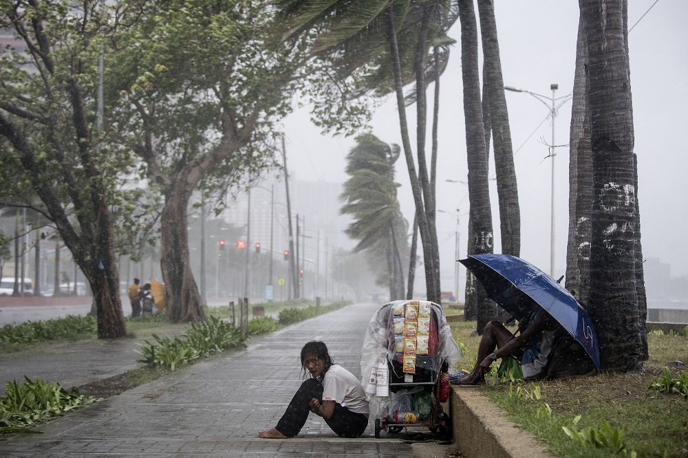A streetside vendor shivers in the rain as weather patterns from Typhoon Yutu affect Manila Bay on October 30, 2018. — AFP pic