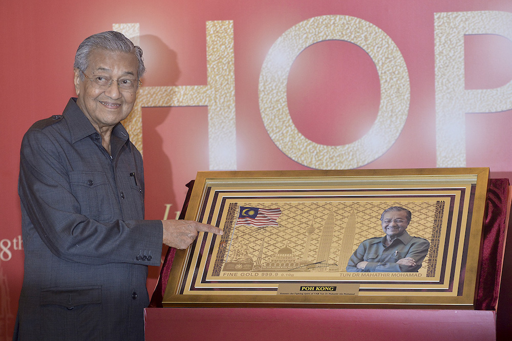 Tun Dr Mahathir Mohamad poses with a replica of Poh Kong's Gold Note of Hope during its official launch in Putrajaya, November 8, 2018. — Picture by Mukhriz Hazim