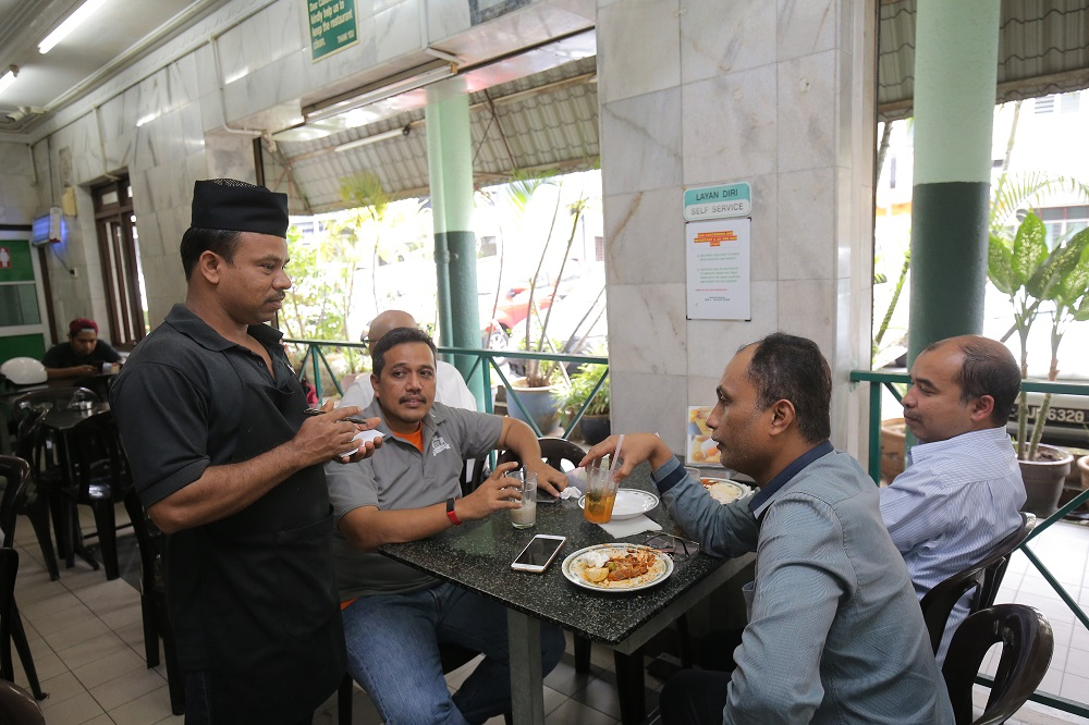A waiter takes the order for a table at Restoran M. Salim in Ipoh November 14, 2018.