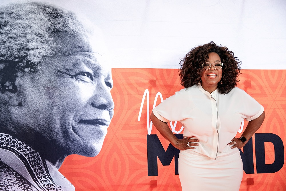 Oprah Winfrey poses next to a banner depicting late former South African president Nelson Mandela at the University of Johannesburg, Soweto Campus, in Johannesburg on November 29, 2018. — GIANLUIGI GUERCIA / AFP pic