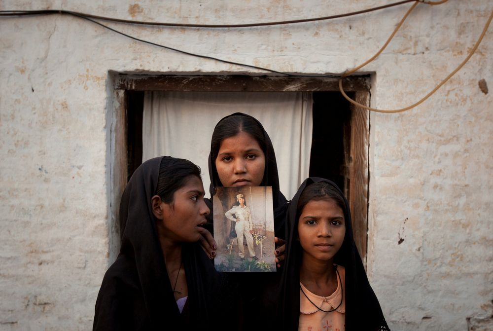 The daughters of Pakistani Christian woman Asia Bibi pose with an image of their mother while standing outside their residence in Sheikhupura located in Pakistan's Punjab Province November 13, 2010. — Reuters pic