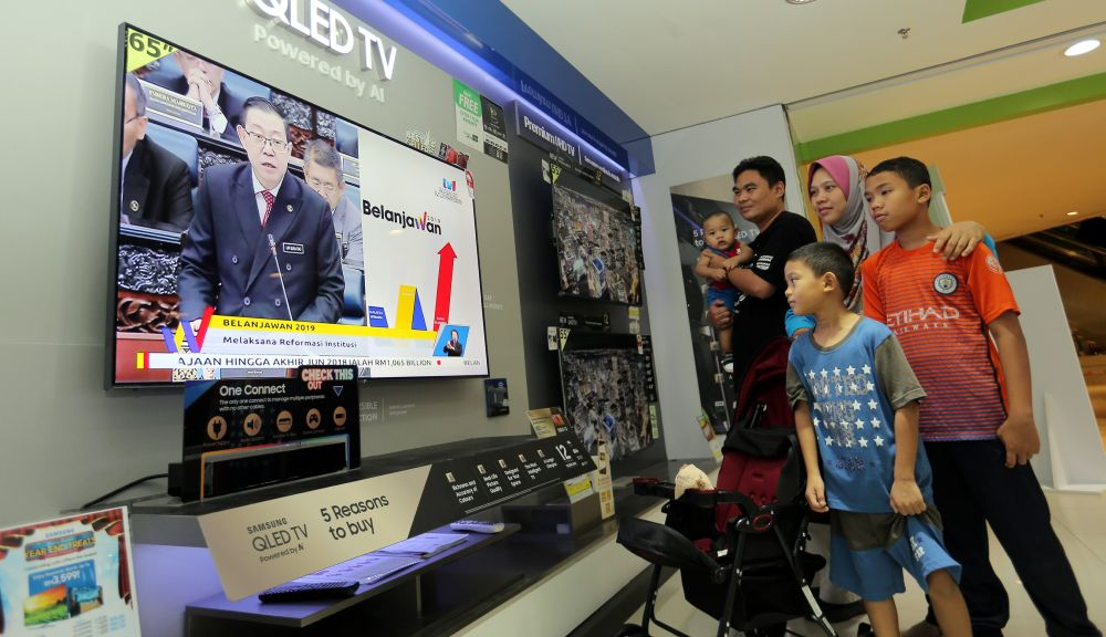 People watch a live television broadcast of Finance Minister Lim Guan Eng tabling Budget 2019 in Parliament November 2, 2018. — Picture by Farhan Najib