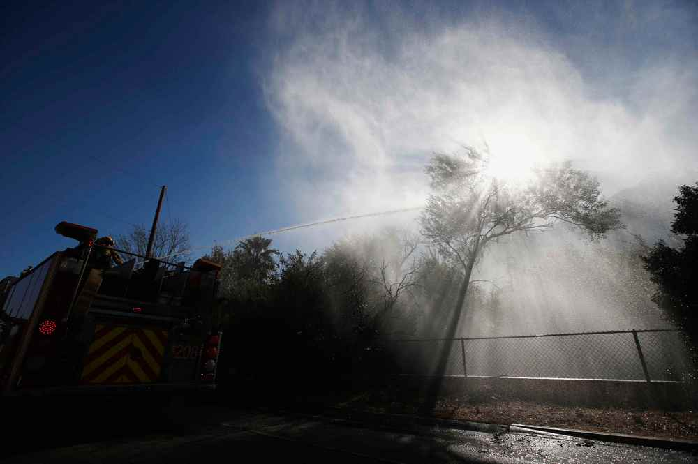 Firefighters spray water from a fire truck as they battle the Woolsey fire in West Hills, Southern California,  November 11, 2018. — Reuters pic