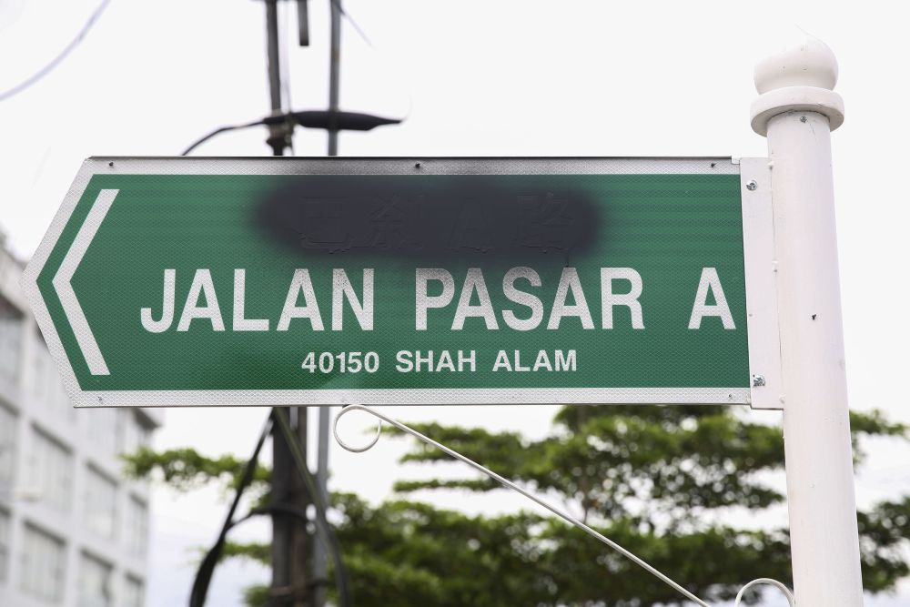 The Chinese characters on a road sign in Shah Alam were sprayed over with black paint.