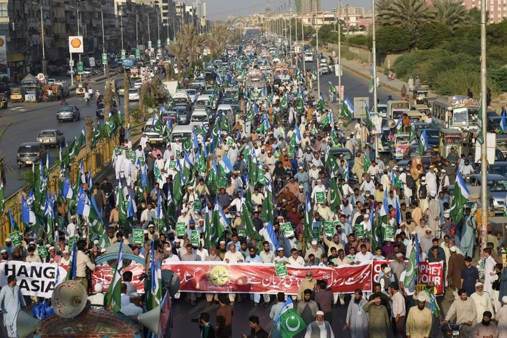 Pakistani supporters of Jamaat-e-Islami (JI) chant slogans and gestures while waving the party flag during a protest following the Supreme Court decision to acquit Asia Bibi of blasphemy, in Karachi, November 4, 2018. — AFP pic