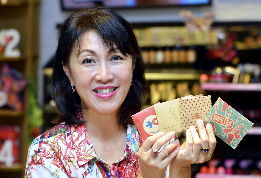 Datin Mina Cheah-Foong with the different packaging that condoms sold at The Body Shop have undergone through the years. — Picture by Ham Abu Bakar